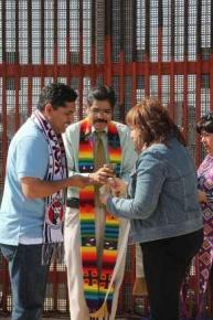 (From left) The Rev. Saul Montiel, Pastor Felipe Ruiz Aguilar and Bishop Minerva Carcaño share communion bread. United Methodist bishops from all over the world visit the U.S. - Mexico border to immerse themselves in the reality of life at the Southern border of the U.S. and sharpen their focus on how the church can be in ministry to persons residing there on May 7, 2013. A UMNS photo by Kathleen Barry.