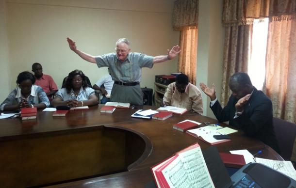 Dr. Lowell Gess prays for Sierra Leone at a weekly devotion held at the United Methodist Church house in Freetown.