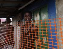 Market workers under Ebola quarantine stand behind orange plastic fencing in Freetown. Video image by Jan Snider, United Methodist Communications.