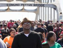 People walk over the Edmund Pettus Bridge in Selma, Ala.,  during the 50th anniversary observance of the