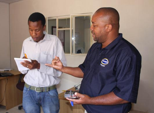 Edwin Ngonyamo, right, chats with an employee at Irvine's Zimbabwe. Ngonyamo was one of 14 students in the first graduating class of Africa University's Faculty of Agriculture. Photo by Vicki Brown, UMNS