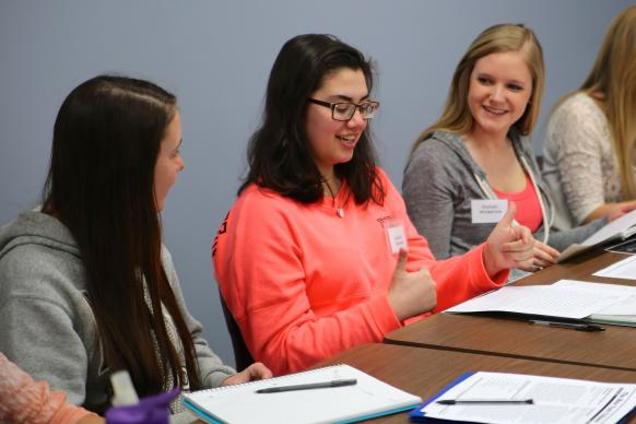 "Ashley Bruce consults with her fellow students Rachel Kanaziz, left, and Kennedy Ervin, right, before presenting her argument in ""The Fredrick Douglass Game"" at Adrian College. Photo by Mike Neal"
