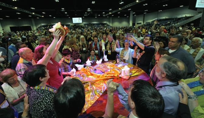 Dozens of demonstrators demanding a more inclusive church took over the floor of a May 3 session of the 2012 United Methodist General Conference in Tampa, Fla. They held Communion around the center table and sang songs, causing the presiding bishop to suspend the morning session. 2012 file photo by Paul Jeffrey, UMNS