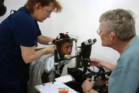 Dr. Gary Fish (right) and assistant Carrie Tarter see a young patient in Highland Park United Methodist Church's eye clinic in Petit-Goâve, Haiti. One of the clinic's buildings was destroyed by the earthquake that rocked Haiti on Jan. 12, 2010, and the church built back, dedicating the new structure on Jan. 12, 2014. File photo courtesy of Highland Park United Methodist Church