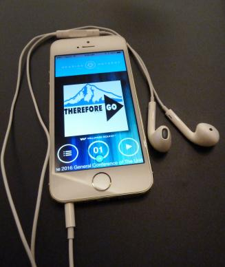 "A smart phone displays the logo ""Therefore Go"" used for the United Methodist General Conference 2016. The headphones and app could provide a ""hearing hotspot"" for translation into different languages.  Photo by Greg Nelson"