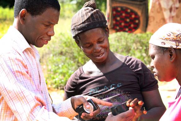 The Rev. Alindo Romão shows mosquito larvaes to women in this 2014 photo. File photo, Imagine No Malaria
