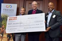 Bishop Thomas Bickerton and the Rev. Gary Henderson (right) present Dr. Mark Dybul, executive director of the Global Fund, with a gift for $9.6 million, a donation from Imagine No Malaria, an initiative of the people of The United Methodist Church to eliminate malaria deaths. Photo by Jay Mallin, UMNS