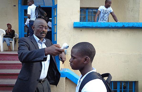 Richard Wiah, president of the College of West Africa, a United Methodist school, checks the temperature of student before he enters the classroom.