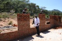 The Rev. Lloyd Nyarota chats with masons who are building walls for the new classrooms at Saungweme Primary School in Zimbabwe. Photo by Vicki Brown, UMNS