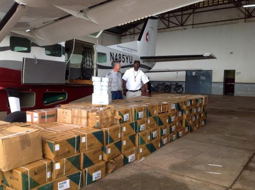 Pilot Gaston Ntambo and a friend look over boxes of fluids for rehydrating cholera patients. Ntambo was flying the fluids from Lumumbashi, Democratic Republic of Congo, to areas along the Congo River where there were cholera outbreaks. Photo courtesy of Betty Kazadi Musau