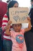 A young migrant girl hoping to reach Germany with her family holds up a sign inside the Hungarian border.  Photo by Oláh Gergely Máté