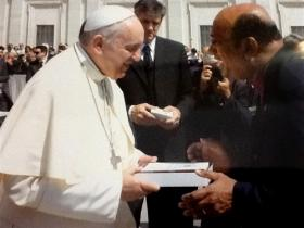 "United Methodist Bishop Sudarshana Devadhar presents copies of ""Celebrating God's Love"" and the United Methodist Book of Worship to Pope Francis during an audience on May 13 in St. Peter's Square at the Vatican. The book includes an essay by the bishop. Photo courtesy of the Vatican."