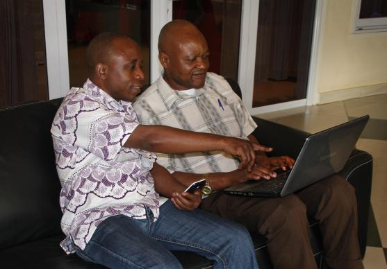 John Kaumba Makulu, left, and the Rev. Chris Tshitenga work together on a video about community health workers and a United Methodist Communications training in Kamina. Tshitenga plans to develop a radio story from the video. Photo by Vicki Brown, UMNS