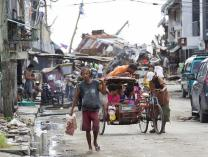 A pedestrian makes his way along a street clogged with storm debris following Typhoon Haiyan in Tacloban, Philippines. 2013 file photo by Mike DuBose, UMNS