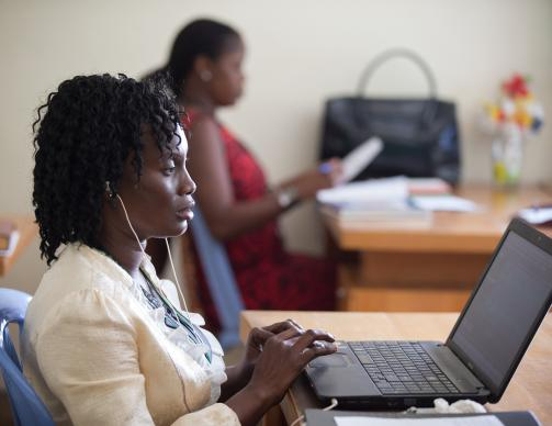 Patricia Ohomon (foreground) edits a story in the newsroom of The United Methodist Church's Voice of Hope radio station in Abidjan, Côte d'Ivoire. Photo by Mike DuBose, UMNS