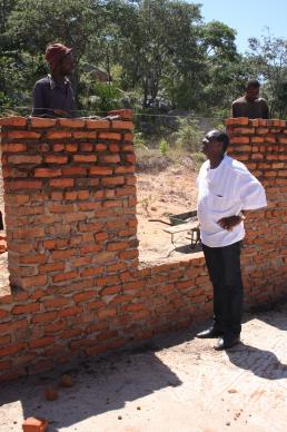 The Rev. Lloyd Nyarota chats with a mason who is building walls for the new classrooms at Saungweme Primary School. Photo by Vicki Brown, UMNS