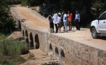Residents who worked on rebuilding a bridge in the Chitora community discuss finishing touches such as guardrails and controlling bank erosion. Photo by Vicki Brown, UMNS