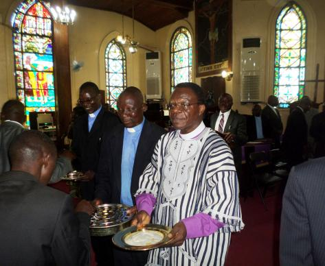 Liberian Area Bishop John G. Innis distributes Holy Communion at First United Methodist Church in Monrovia during a special service that marked his 2015 return from the United States, where he stayed for months for health reasons and restrictions due to the Ebola crisis. Innis is one of four African bishops scheduled to retire this year.