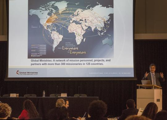 Thomas Kemper delivers his address with the map showing the locations of United Methodist missionaries around the world.