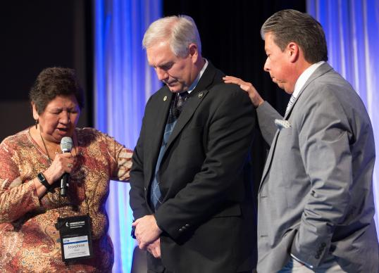 Josephine Deere (left) and the Rev. David Wilson (right) of the Oklahoma Indian Missionary Conference pray for the Rev. Tom Albin during a panel about praying for General Conference at the pre-General Conference briefing in Portland, Ore. Photo by Mike DuBose, UMNS