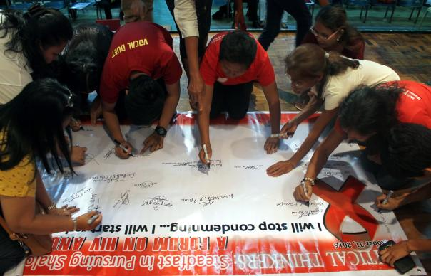 Participants sign a banner with a public statement to