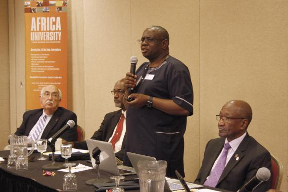 Munashe Furusa, vice chancellor of Africa University, said the United Methodist university is open and operating smoothly despite political unrest in Zimbabwe, although some students have been unable to register for financial reasons. Retired Bishops J. Lawrence McClesky (left) and Ernest Lyght (middle left) and Marcus Matthews (right) listen to Furusa's report. Photo by Vicki Brown, UMNS.
