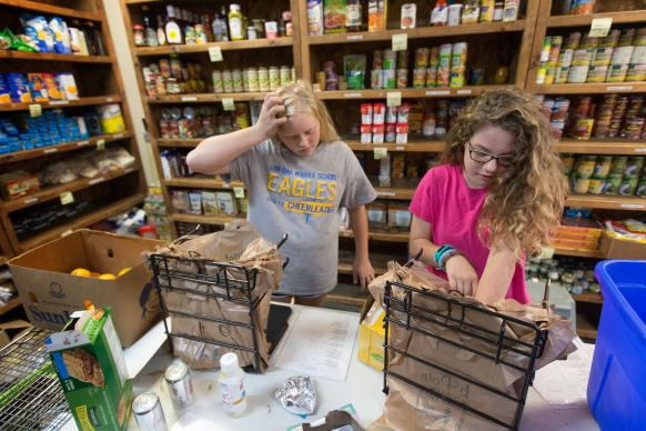 Volunteers Abby Couvillion (left) and Kyleigh Overheim work in the food pantry at Live Oak United Methodist Church in Watson, La. The 12-year-olds were out of school due to flooding in southern Louisiana and elected to spend their time in the church food pantry to help those in need during the recovery.