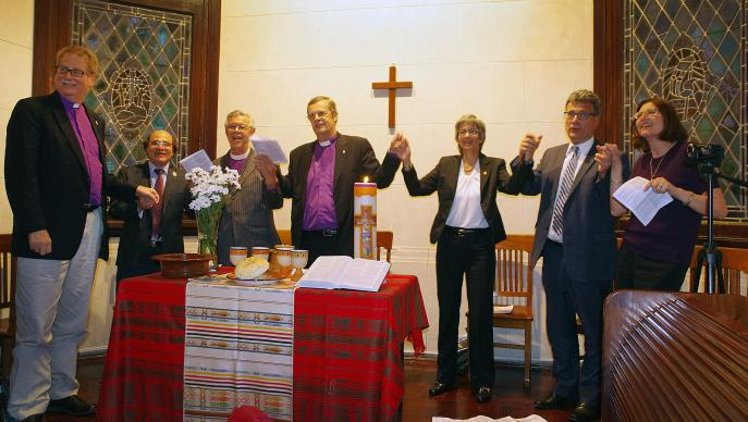 The opening of the United Methodist Global Ministries and Upper Room regional office in Bueno Aires, Argentina, is celebrated with song. (From left) Bishop Ken Carter (United Methodist Church), Bishop Adriel de Souza Maia (Brazilian Upper Room), Bishop Stanley S Moraes (Methodist Church of Brazil), Bishop Frank de Nully Brown (Argentinian Evangelical Methodist Church), Bishop Hope Morgan Ward (President of Global Ministries), Thomas Kemper (top executive of Global Ministries) and Sarah Wilke (Upper Room). Photo by Gustavo Vasquez, UMNS