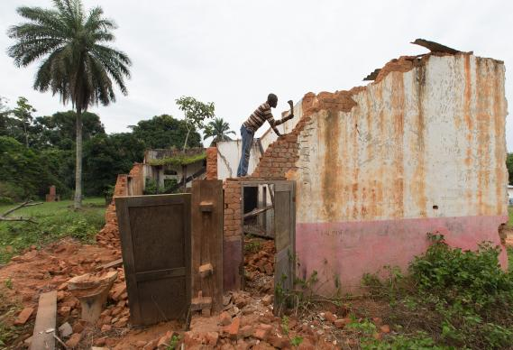A worker salvages bricks with a machete on the grounds of The United Methodist Church's Tunda Hospital in the Democratic Republic of Congo.