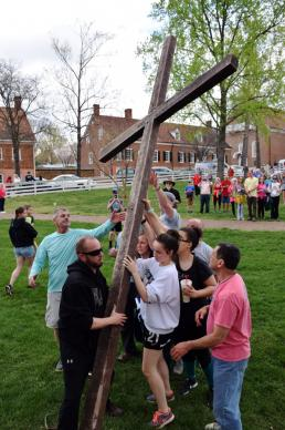 Participants in Trinity Moravian Church's annual Good Friday Crosswalk in Winston-Salem, N.C., raise the cross in Salem Square. Photo by Andrew David Cox, Moravian BCM