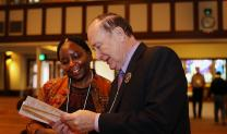 Dr. Pauline Muchina and the Rev. Donald E. Messer look over the program before the start of