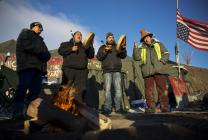 Native Americans from left, Eugene Sanchez, Jason Umtuch, Martan Mendenhall, and Hugh Ahnatock, all of Portland, Ore., drum and sing at the Oceti Sakowin camp where people have gathered to protest the Dakota Access oil pipeline in Cannon Ball, N.D., Sunday, Dec. 4, 2016. The U.S. Army Corps of Engineers said Sunday that it won't grant an easement for the Dakota Access oil pipeline in southern North Dakota, handing a victory to the Standing Rock Sioux tribe and its supporters, who argued the project would threaten the tribe's water source and cultural sites. Photo by David Goldman, AP