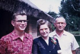 1955 Bill Lovell and his Mother and Father Eloise and Marshall Lovell standing in front of their home at Wembo Nyama. Photo courtesy of Bill Lovell