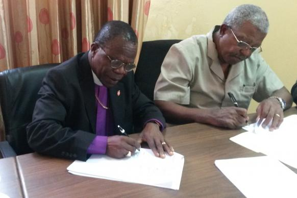 Bishop John Innis signs the construction contract for a commercial building that The United Methodist Church Liberia hopes will generate income to support the ministry of the church. Next to him is John Togba, co-chairman for the Liberia United Methodist Empowerment Foundation. Photo by Julu Swen, UMNS