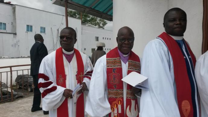 Bishop John Innis, left, Bishop Arthur Kulah, middle, and the Rev. Christopher Marshall, right, process in for the ceremony to install Kulah as interim bishop of the Liberia Conference. Photo by Julu Swen, UMNS.