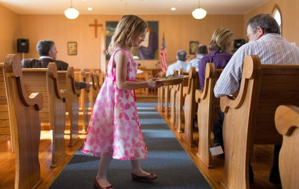 Elizabeth Knotts, 6, collects the offering at New Hope Valley United Methodist Church in Valley Furnace, W.Va., in 2015.  If the proposed budget passes the 2016 General Conference, conferences will be asked to pay less to support the general church. File photo by Mike DuBose, UMNS