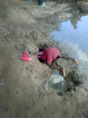 A girl burrows in the riverbed for water to drink. Dindi school children are risking their health and their lives drinking this unsafe water, which was their only option in March. Photo by Luckymore Mudzengerere, UMNS.