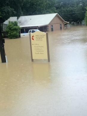 Recent flooding in Denham Springs, Louisiana, at one point nearly covered a sign for the First United Methodist Church there. The home in the background belongs to a member of that church. Photo courtesy of the Rev. Jackie King