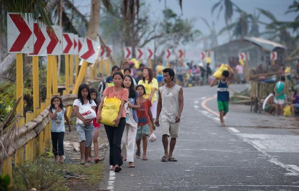 Survivors of Typhoon Haiyan leave with emergency food rations provided by the United Methodist Committee on Relief following a distribution in Dagami, Philippines, in 2013. File photo by Mike DuBose, UMNS