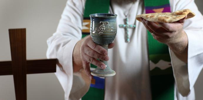 A member of the clergy holds up the elements of Holy Communion. In 2005, the average age of retiring United Methodist elders was 64, but by last year that had climbed to 66, the Lewis Center found in analyzing data provided by Wespath Benefits and Investments, formerly the United Methodist Board of Pension and Health Benefits. Photo illustration by Kathleen Barry, United Methodist Communications