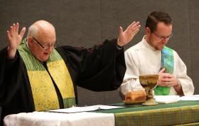 Bishop Mike Lowry and Deacon Jackson Henry preside over the May 20 communion service at the 2016 United Methodist General Conference in Portland, Ore. Photo by Kathleen Barry, UMNS