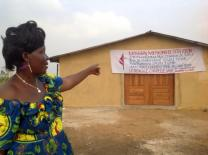 Henriette Awuy points to the new church building for Bita United Methodist Church. She donated money and sheet metal for the building.