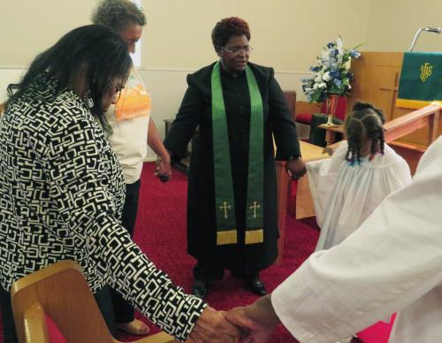 The Rev. Doris Smith leads some members of Warren Chapel United Methodist Church, in Terrell, Texas, in prayer on Sept 11. Smith is a full-time Dallas police detective and serves as the church's part-time pastor. Photo by Sam Hodges, UMNS.