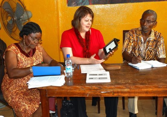 Robin Pippin (center) from United Methodist Discipleship Ministries demonstrates to lecturers how to use e-readers  while the Rev.Olivia Wesley (left), principal of the College of Theology and Management and Church Training Centre, takes notes. Julu Swen (right) looks on. Photo by Phileas Jusu, UMNS