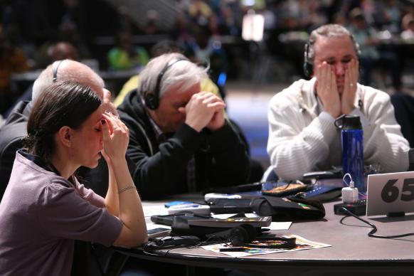 Delegates pause for a moment of prayer following the morning discussion and expressions of confusion in the May 12 plenary at the 2016 United Methodist General Conference. From left are Vasylyna Babych from the Ukraine-Moldava Provisonal Conference and Alexander Pererva and Alexandr Meinikov from the Southern Russia Provisonal Conference. Photo by Kathleen Barry, UMNS