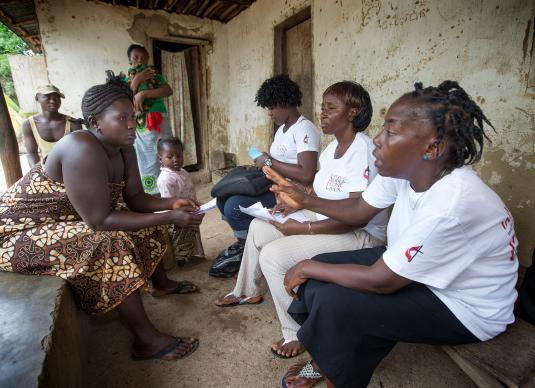 Health worker Kadie E. Koroma (right), part of a team with the United Methodist Church's Imagine No Malaria campaign, processes a voucher that will provide mosquito nets for the family of Gbassay Foday (seated at left) for her home in Baoma village, near Bo, Sierra Leone, in June 2014. The campaign had raised more than $68 million by the end of 2015. File photo by Mike DuBose, UMNS