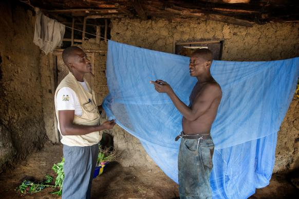 Ernest Jusu (left), a nurse working with the United Methodist Church's Imagine No Malaria campaign, explains the proper use of the new insecticide-treated mosquito nets that Peter Braima received for his family in Manjama village, near Bo, Sierra Leone, in June 2014. File photo by Mike DuBose, UMNS