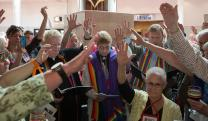 Supporters gather around Susan Laurie (center) during a service of Holy Communion on the first day of the 2016 United Methodist General Conference in Portland, Ore. Laurie, a lesbian, was ordained in an unauthorized service in the lobby of the Oregon Convention Center. Photo by Mike DuBose, UMNS.