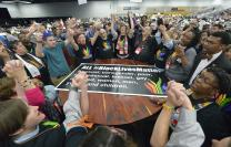 Members of the Black Lives Matter movement disrupt the May 16 proceedings of the 2016 United Methodist General Conference in Portland, Ore. The demonstrators marched into the plenary session chanting slogans and gathered around the central communion table. Photo by Paul Jeffrey, UMNS.