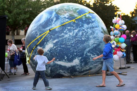 Children get a closer look of a large inflatable globe during the May 12th General Conference Climate Vigil at Oregon Convention Center Plaza in Portland. Photo by Kathleen Barry, UMNS
